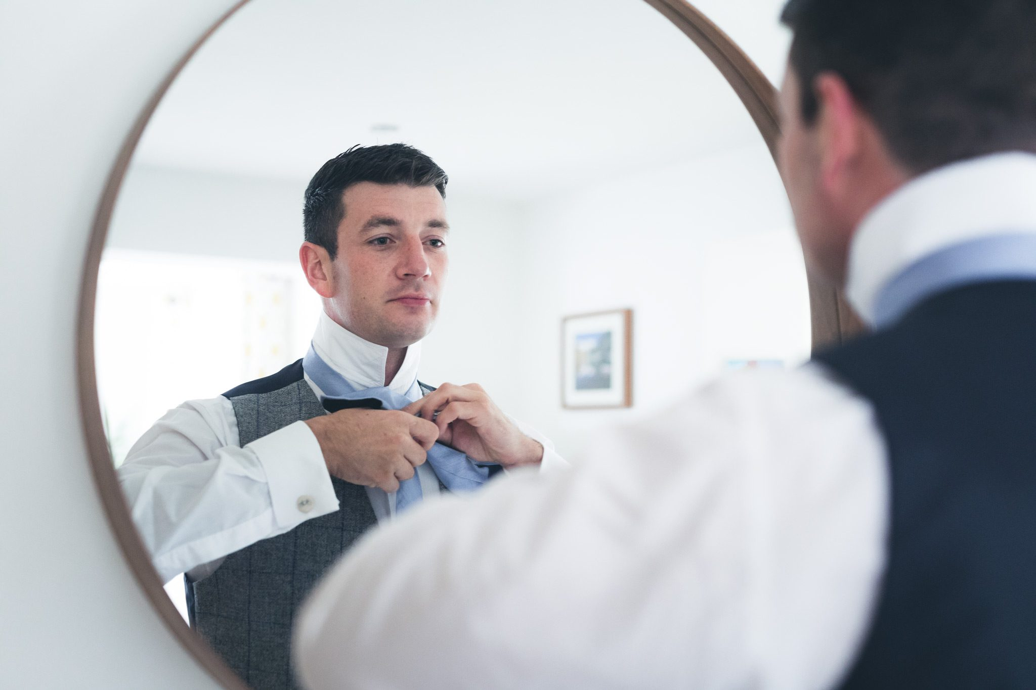 Photo of the groom looking in the mirror